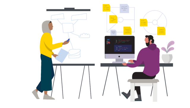 A woman draws a system on a flipchart while a man works on a computer