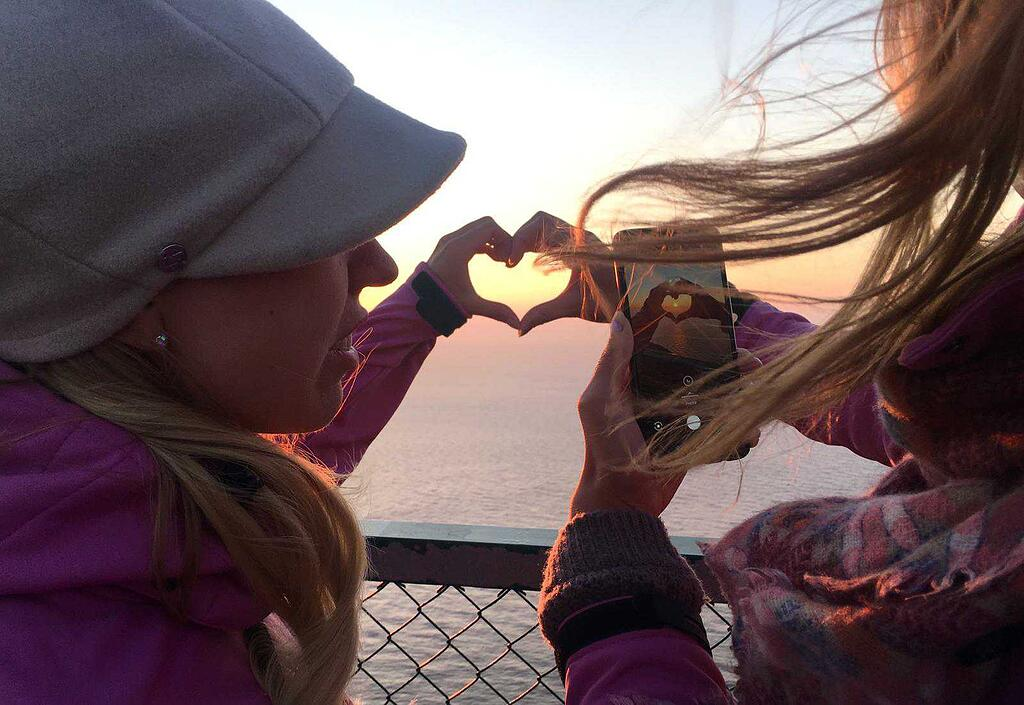 Two women take a photo of their hands making a heart shape at sunset
