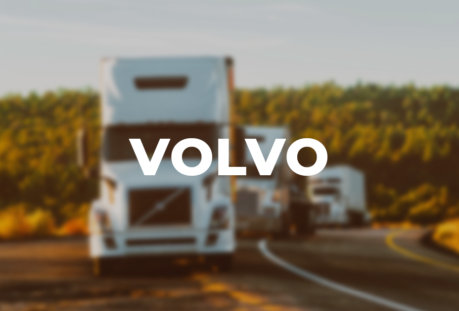 Volvo written on top of a blurred image of trucks on the road