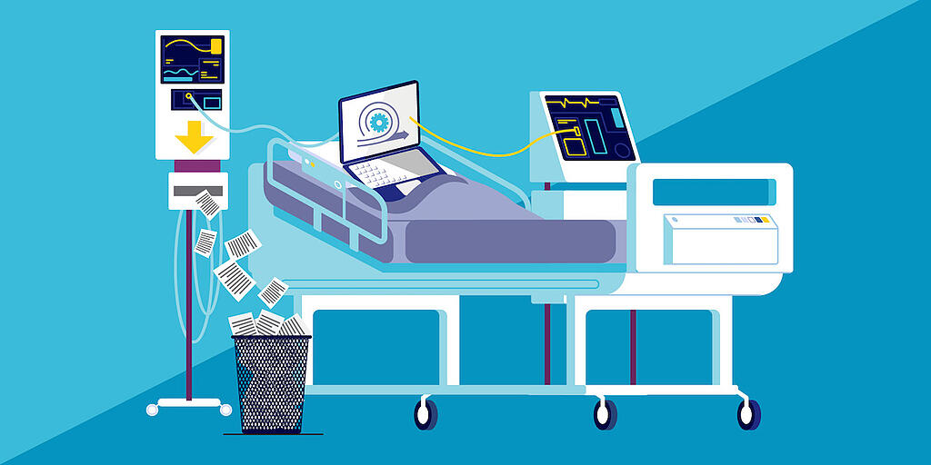 A laptop on a hospital bed connected to machines