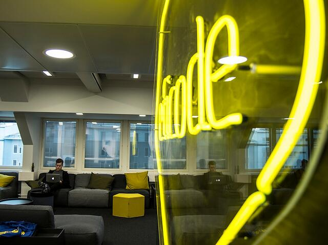 A person reading on a laptop at the eficode office with a large neon eficode logo