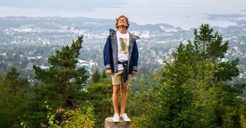 Hans is a DevOps and Continuous Delivery consultant at Eficode's Norway office. He's standing on a tree trunk looking at the sky with a view over Oslo.
